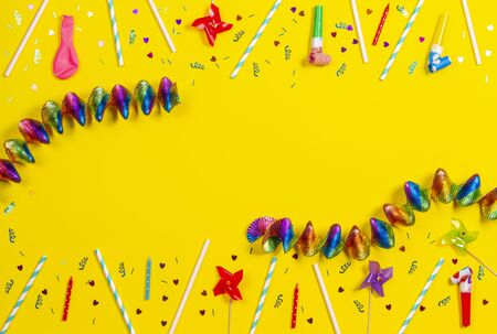 Bithday party decorations on yellow background, top view.