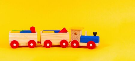 Wooden toy train with colorful blocks on yellow background Banque d'images - 132050234