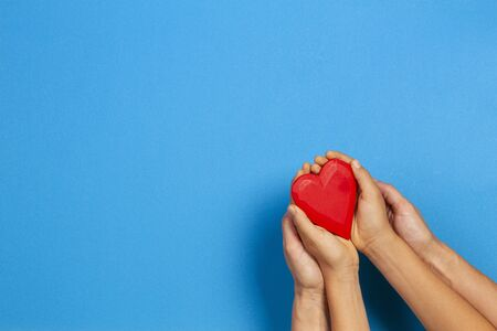 Adult and child hands holding red heart over blue background. Love, healthcare, family, insurance, donation concept Imagens
