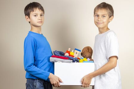 Donation concept. Kids holding donate box with books, clothes and toys