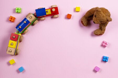 Baby kids toys background. Teddy bear, wooden train and colorful blocks on light pink background