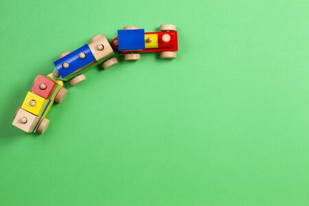 Wooden toy train with colorful blocks on light green background. Top view