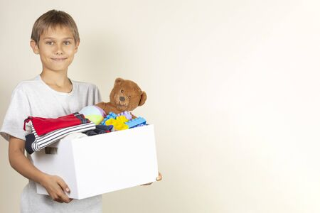 Donation concept. Kid holding donate box with books, clothes and toys