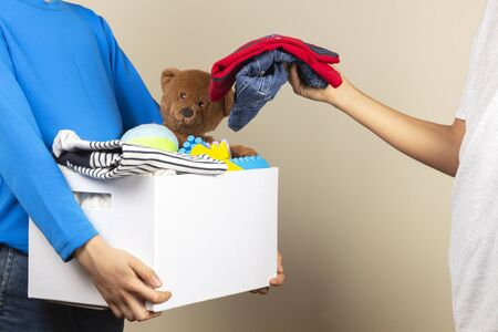 Donation concept. Kid hands collect donate box. Donation cardboard full of books, clothes and toys