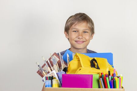 Donation concept. Kid holding donate box with books, pencils and school supplies Stock Photo
