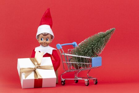 Christmas shopping concept. Mini shopping cart and little Christmas tree with present box and funny toy elf on red background