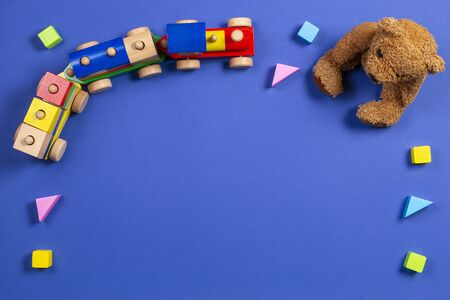 Baby kids toys background. Teddy bear, wooden train and colorful blocks on navy blue background