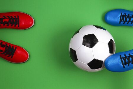 Top view to soccer ball between soccer players feets on green background