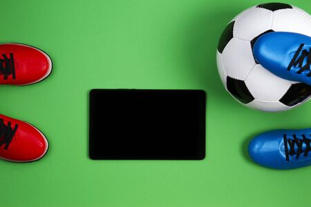 Soccer football background. Soccer boots, ball and tablet computer on green background Stock Photo