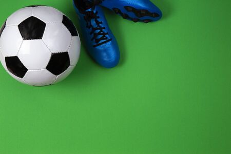 Soccer football player shoes with soccer ball on green background. Stock Photo