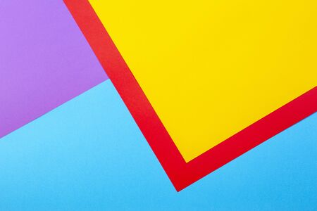 Color papers geometry flat composition background with yellow red violet and blue tones. Stock Photo