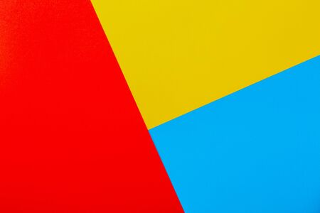 Color papers geometry flat composition background with yellow red and blue tones. Stock Photo