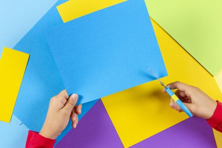 Kids hands cutting colored paper with scissors. Top view 스톡 콘텐츠