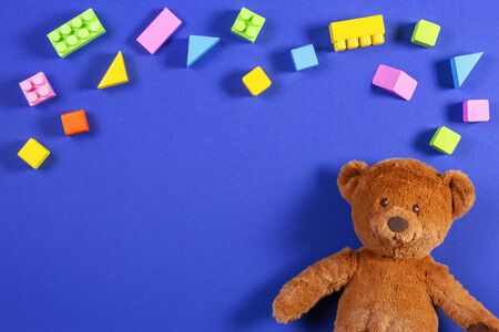 Baby kids toys frame with teddy bear and colorful wooden blocks and cubes on blue background