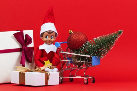 Christmas shopping concept. Mini shopping cart, little Christmas tree with bauble, present box and funny toy elf on red background
