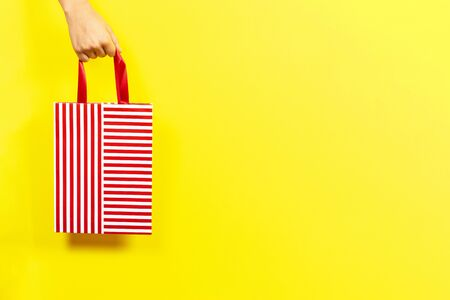 Hand holding red striped present gift bag over yellow background. Shopping, holiday, donation concept Stock Photo