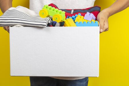 Donation concept. Kid hands holding donate box with books, clothes and toys ober yellow background Stock Photo