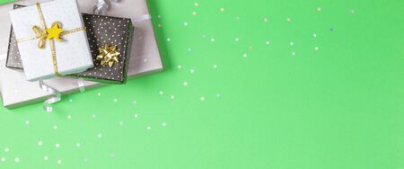 Christmas present wrapped gift paper decorated with ribbon on green background with sparkling glitter stars. Top view