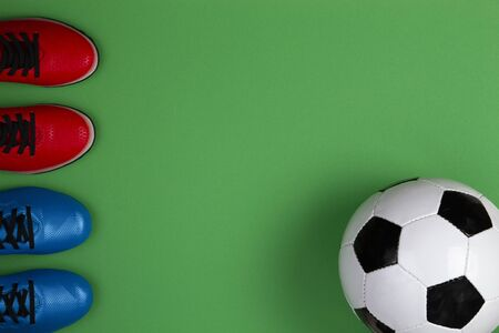 Soccer football sport background. Top view to soccer ball and fotball boots on green background
