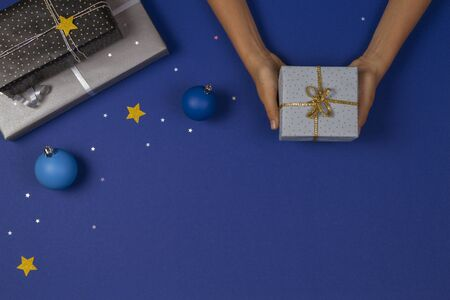 Christmas background. Top view to hands holding Christmas presents on blue background with sparkling glitter stars and bauble decoration Stock fotó