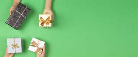 Hands holding presents wrapped in gift paper on light green background. Christmas, New Year, holidays concept Stock Photo