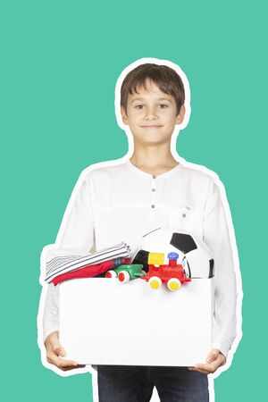 Donation concept. Kid holding donate box with clothes, books, school supplies and toys. Magazine collage style with light green color background Stockfoto