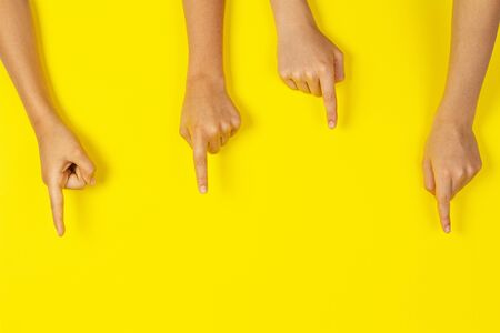 Many kids hands pointing to something on yellow background Stock Photo