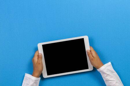 Child hand holding white tablet computer on light blue background