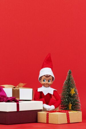 Christmas background. Stack of Xmas present boxes and sitting toy elf on red background Zdjęcie Seryjne