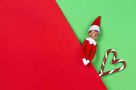 Christmas background. Toy santa elf and candy canes on red and green background. Top view
