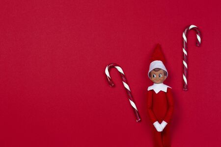 Christmas background. Little toy elf and candy canes on red background. Top view Zdjęcie Seryjne