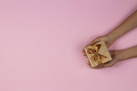 Hands holding small gift presents box over light pink background. Top view
