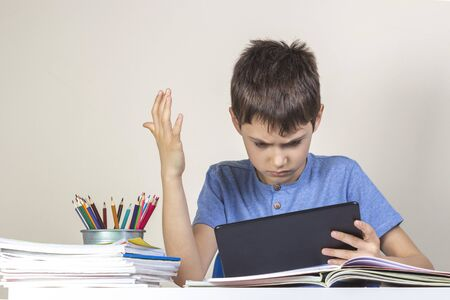 Sad confused child with tablet computer sitting at table with books notebooks Reklamní fotografie - 133483882