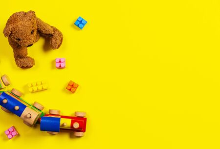 Baby kids toys background. Teddy bear, wooden train and colorful blocks on yellow background