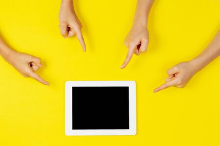 Many kids hands pointing to tablet computer on yellow background Reklamní fotografie - 133483885