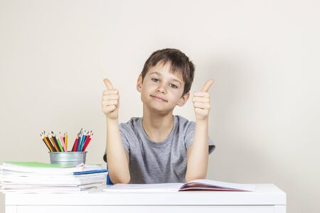 Happy boy making homework tasks and showing thumbs up sign