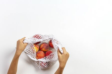 Hands holding mesh glocery shopping bag with fresh peaches on white background. Top view Reklamní fotografie - 133483790