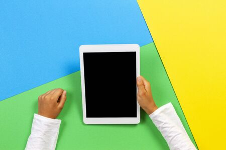 Hands holding tablet computer on yellow, blue and green background. Top view 版權商用圖片