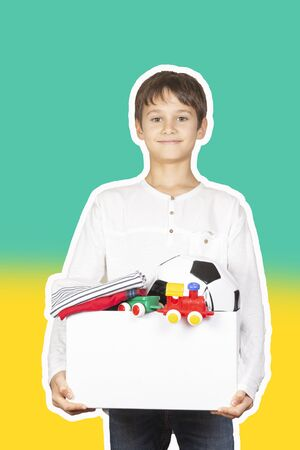 Donation concept. Kid holding donate box with clothes, books, school supplies and toys. Magazine collage style with light green and yellow color background Reklamní fotografie - 133483793