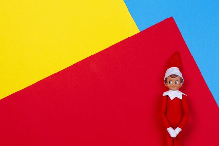 Christmas background. Christmas toy decoration Santa elf on red yellow and blue background. Top view Reklamní fotografie - 133483795