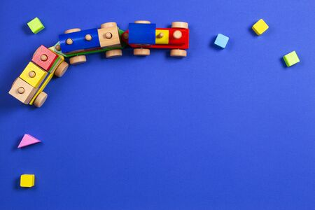 Wooden toy train with colorful blocks on blue background. Top view