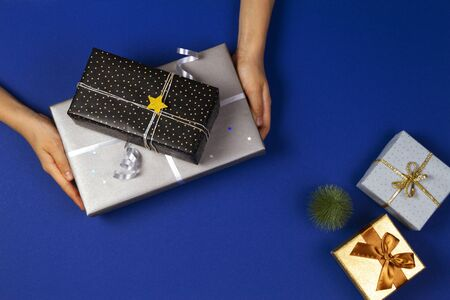 Hands holding presents wrapped in gift paper on navy blue background. Christmas, New Year, holidays concept 版權商用圖片