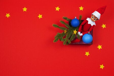 Christmas background. Red toy Santa eff sitting in present box with green fir branch and decoration bauble on red background. Top view Zdjęcie Seryjne