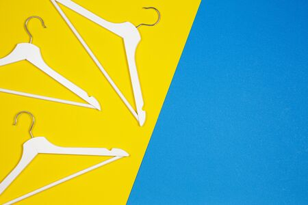 White wooden clothes hangers on yellow and light blue background. Top view. Shopping, sale, promo, new season concept