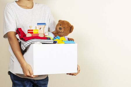 Donation concept. Kid hands holding donate box with books, clothes and toys