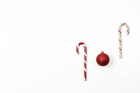 Minimal Christmas background. Traditional Christmas sweets, candy cane with red decoration bauble ball on white background Reklamní fotografie - 133483806