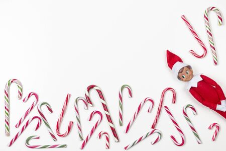 Christmas background. Top view to many candy canes and little toy Santa elf on white background
