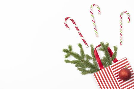 Christmas present gift bag with fir tree branch, candy canes and Xmas decoaration bauble on white background