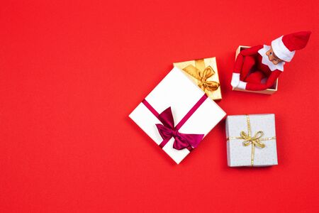 Christmas present background. Red toy Santa elf sitting in present gift box on red background. Top view Zdjęcie Seryjne