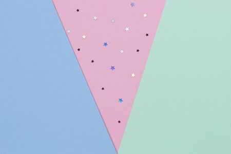 Abstract geometric festive pastel color paper background with glitter stars. Top view